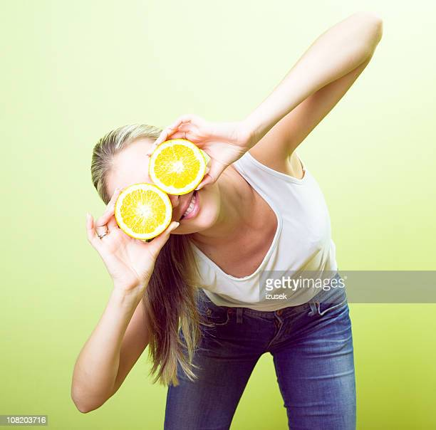 Woman Holding Orange Halves in Front of Eyes