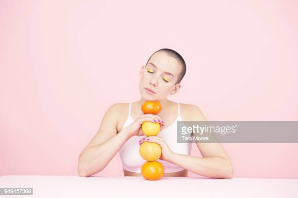woman holding oranges - androgynous stock pictures, royalty-free photos & images