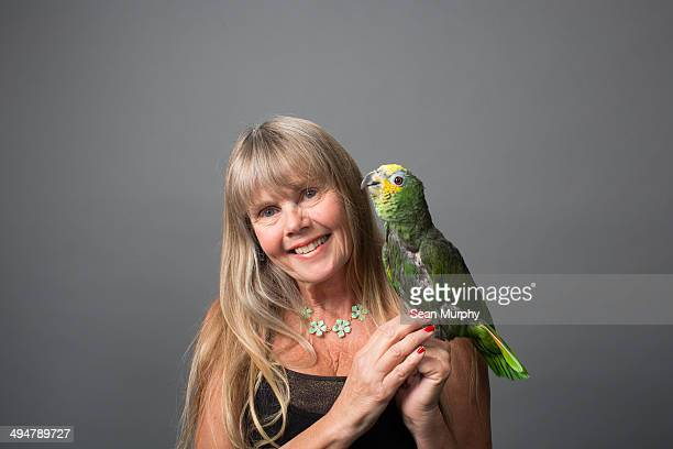 Woman holding Orange-winged Parrot