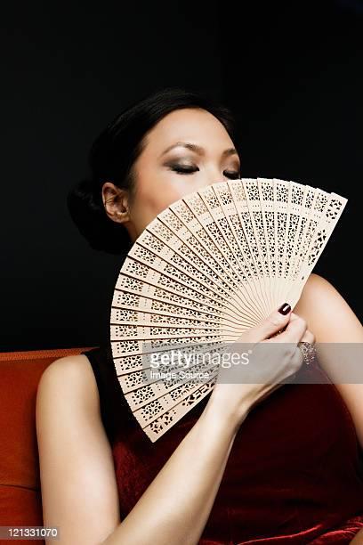 Woman holding oriental fan, portrait