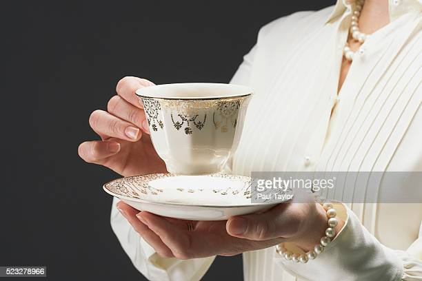 woman holding ornate gilded tea cup and saucer - porcelain stock pictures, royalty-free photos & images