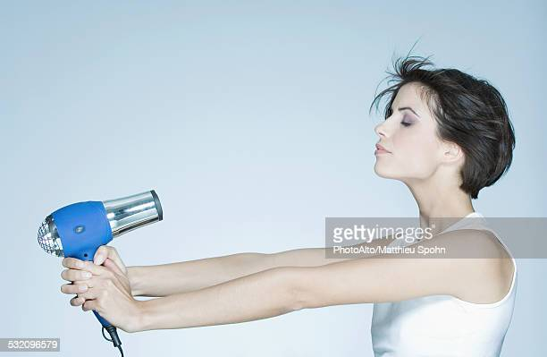 Woman holding out hair dryer, profile