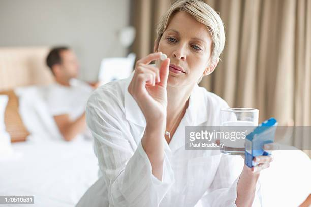 Woman holding out medicine tablet