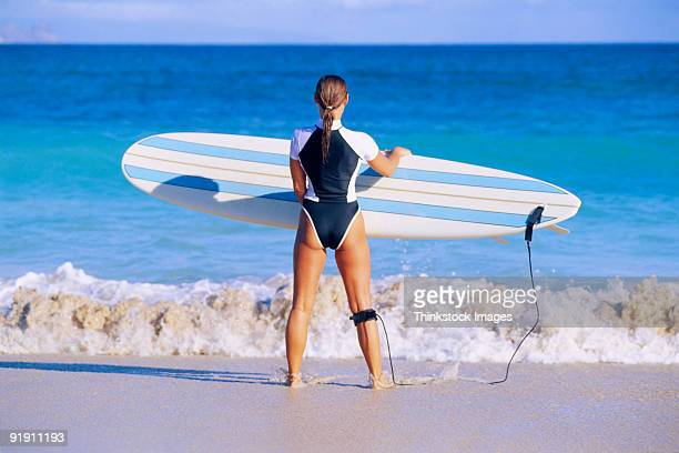 woman holding out surfboard, approaching water - thinkstock foto e immagini stock