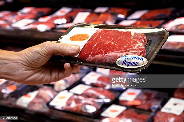 woman holding packet of beef in supermarket - meat stock pictures, royalty-free photos & images