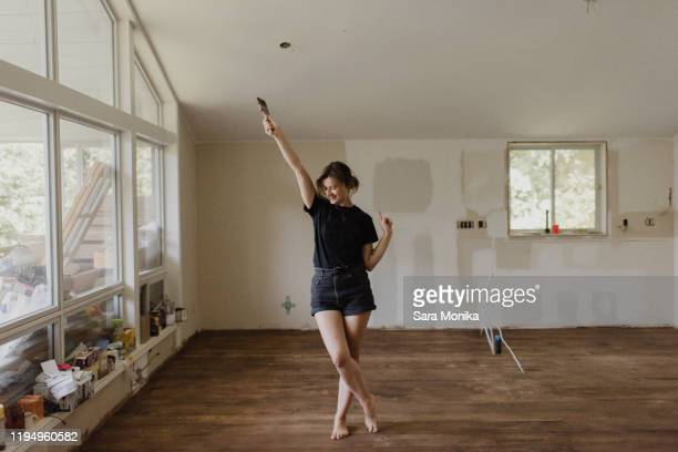 woman holding paintbrush and dancing in new home - life events stock pictures, royalty-free photos & images
