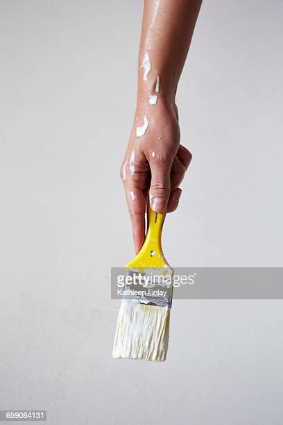 woman holding paintbrush with white paint, close-up - paintbrush stock pictures, royalty-free photos & images