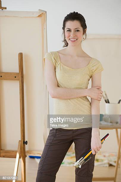 Woman holding paintbrushes in front of easel