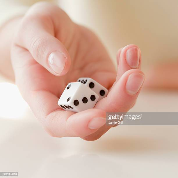 Woman holding pair of dice