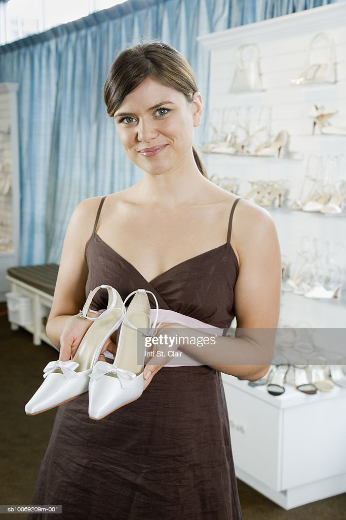 Woman holding pair of high heeled shoes in wedding shop, portrait : Stockfoto