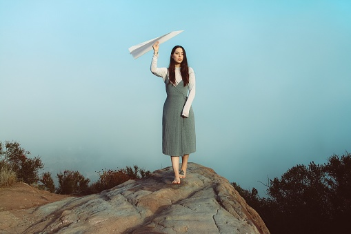 Woman Holding Paper Airplane While Walking On Rock Against Sky During Sunset - gettyimageskorea