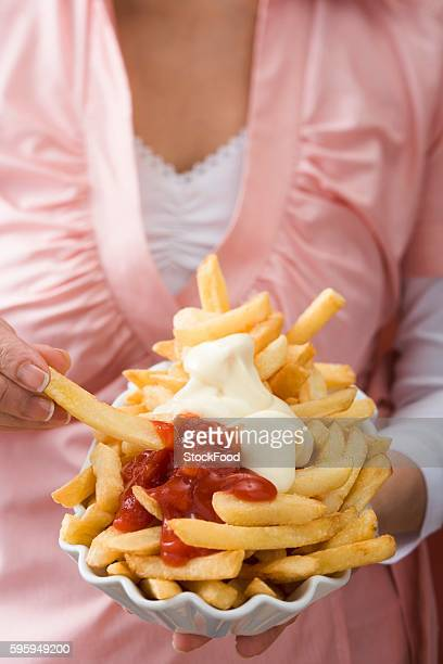 Woman holding paper dish of chips with ketchup & mayonnaise