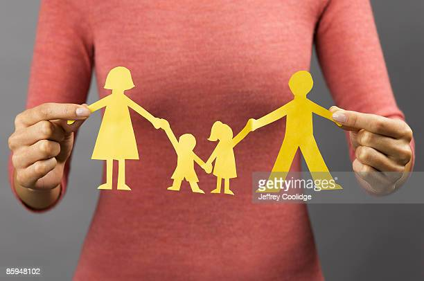 Woman Holding Paper Doll Family