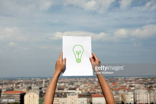 Woman holding paper green light