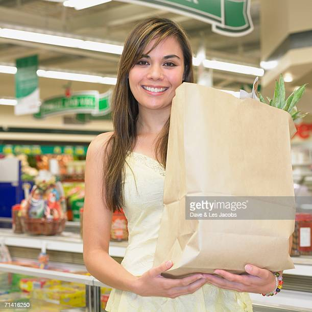 Woman holding paper grocery bag at supermarket