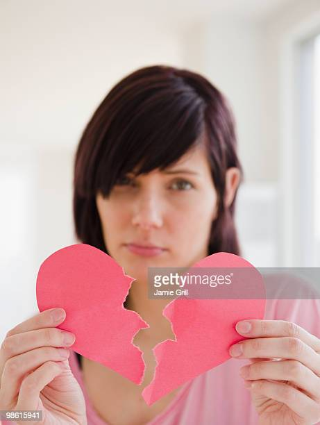 Woman holding paper heart ripped in half