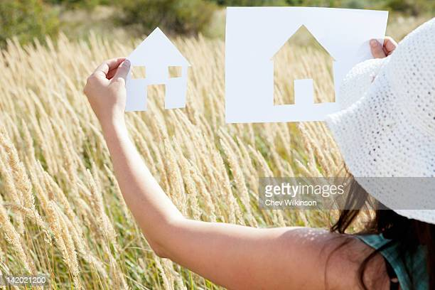 Woman holding paper house cut outs
