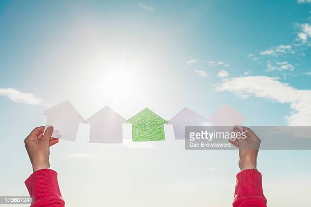 Woman holding paper houses in sky