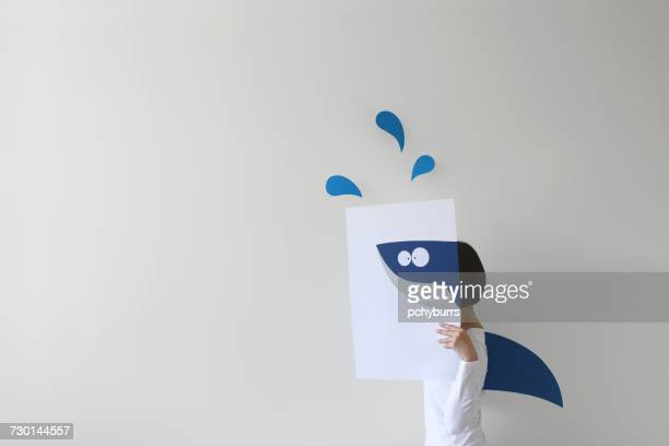 Woman holding paper with a shark drawing and wearing a shark fin