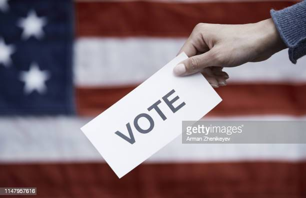 woman holding paper with vote text on american flag background - presidential election stock pictures, royalty-free photos & images