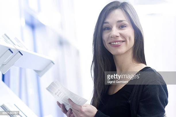 woman holding paperwork looking at camera smiling - sigrid gombert stockfoto's en -beelden