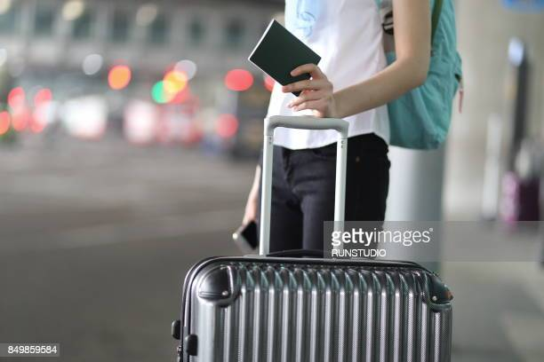 woman holding  passport and luggage at at bus station - luggage stock photos and pictures