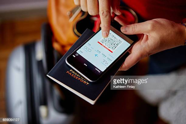 woman holding passport and smartphone, smartphone showing qr code, overhead view - passeport photos et images de collection