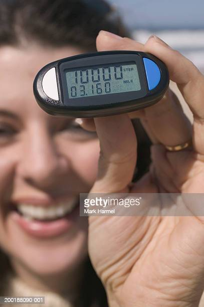 Woman holding pedometer, smiling (focus on pedometer)