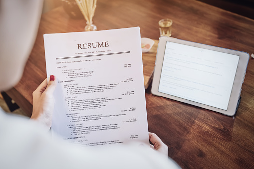 woman holding pen over resume application with smart phone and using computer laptop to job search on online internet. applying for a job concept. 1065170540