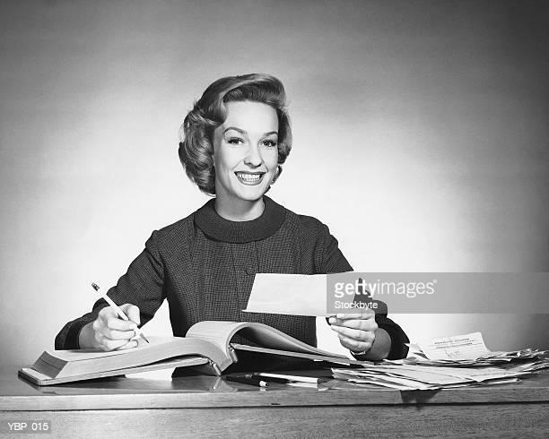 Femme tenant un crayon et papier, livre ouvert sur le devant.