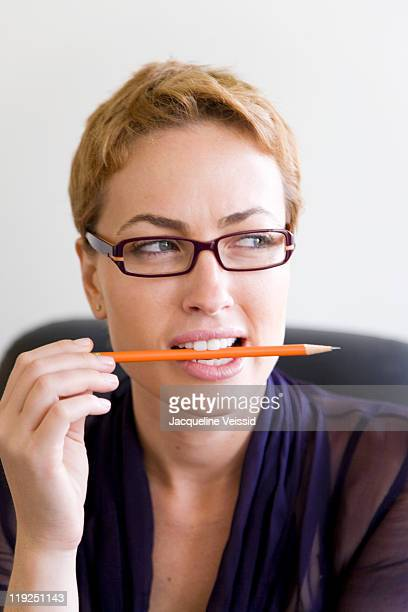 Woman holding pencil between teeth looking away