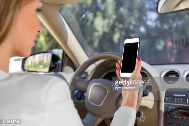 Woman holding phone in car clipping path white screen