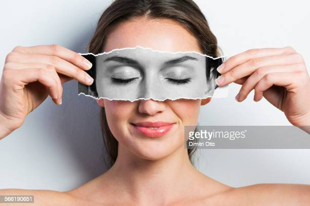 Woman holding picture of closed eyes over hers