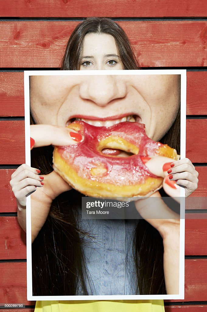 woman holding picture of woman eating donut : Stock Photo