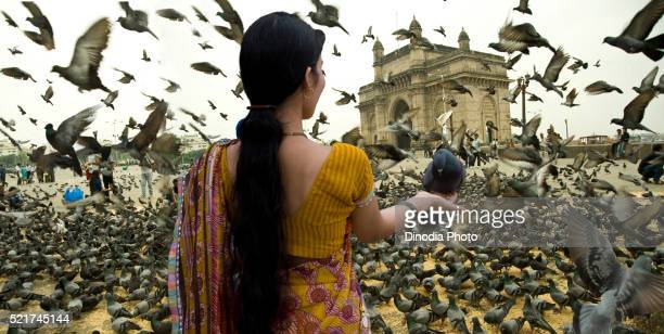 Woman holding pigeon in hand, maharashtra, India