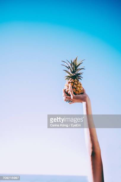 Woman Holding Pineapple Against Clear Blue Sky
