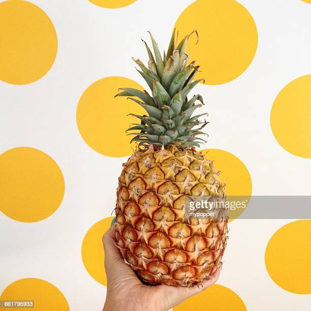 Woman holding pineapple in front of  yellow spot background