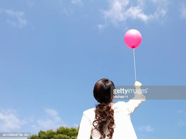 Woman holding pink balloon, low angle view, rear view
