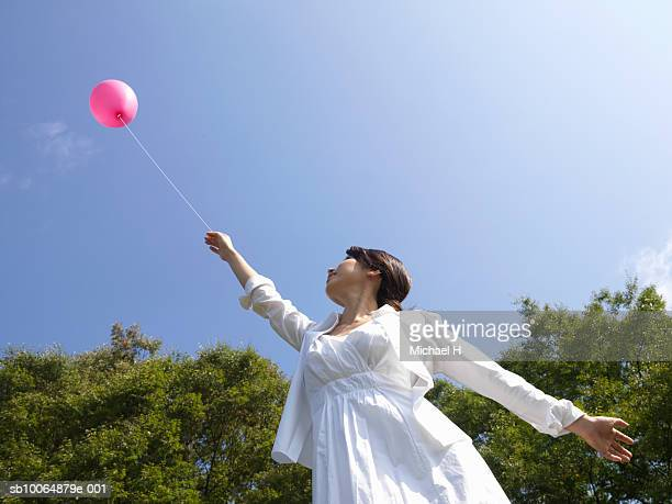 Woman holding pink balloon outdoors, low angle view