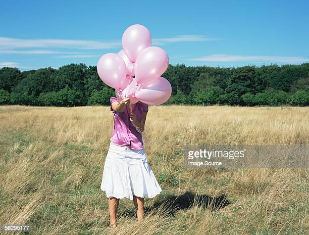 Frau hält Rosa Ballons
