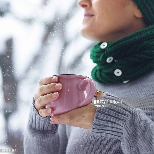 Woman holding pink cup of coffee in her hands
