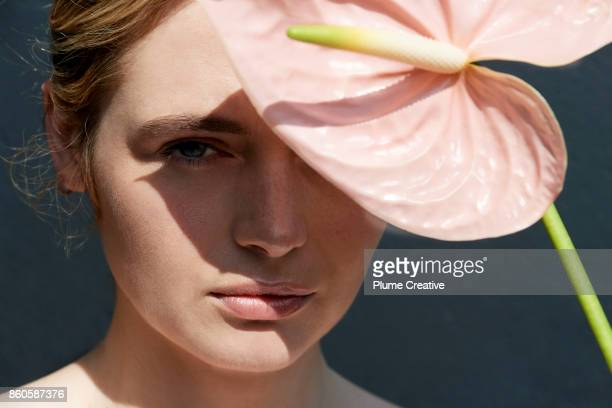Woman holding pink flower over face