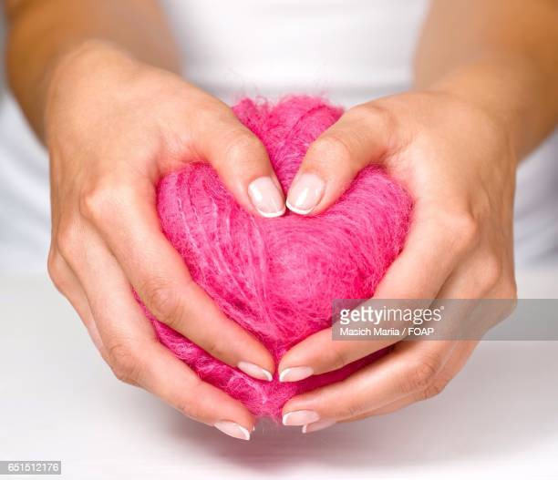 Woman holding pink heart shape ball of wool