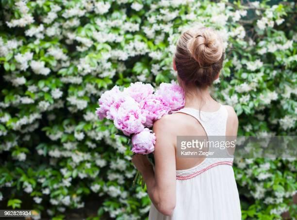 woman holding pink peonies , rear view - pivoine photos et images de collection