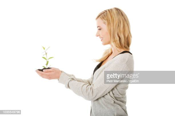 woman holding plant against white background - 袖 ストックフォトと画像