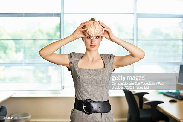 woman holding plastic brain in front of her head