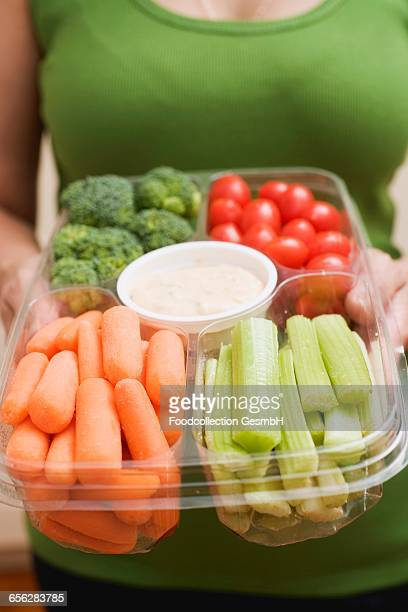Woman holding plastic tray of vegetables and dip