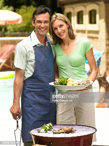 Woman holding plate, man cooking food on bbq, smiling, portrait