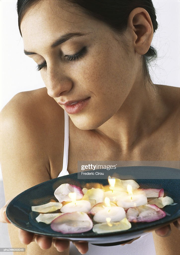 Woman holding plate of candles and rose petals, looking down, close-up : Stockfoto