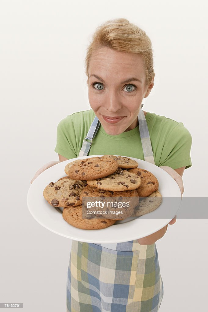 Woman holding plate of cookies : Stockfoto